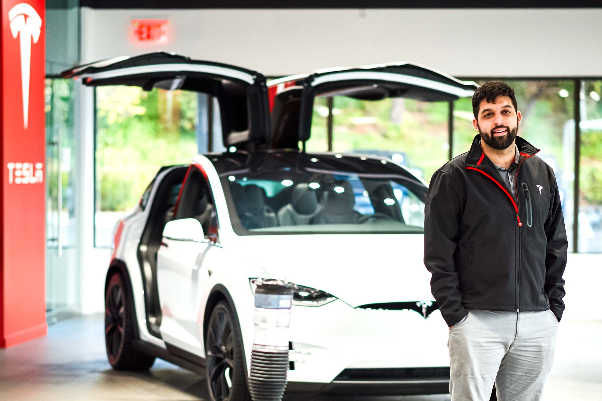 Jacob Redding in front of a white Tesla vehicle