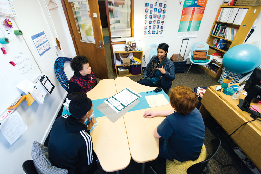 Lisa Lucas meets with a group of students at Jane Adams Middle School