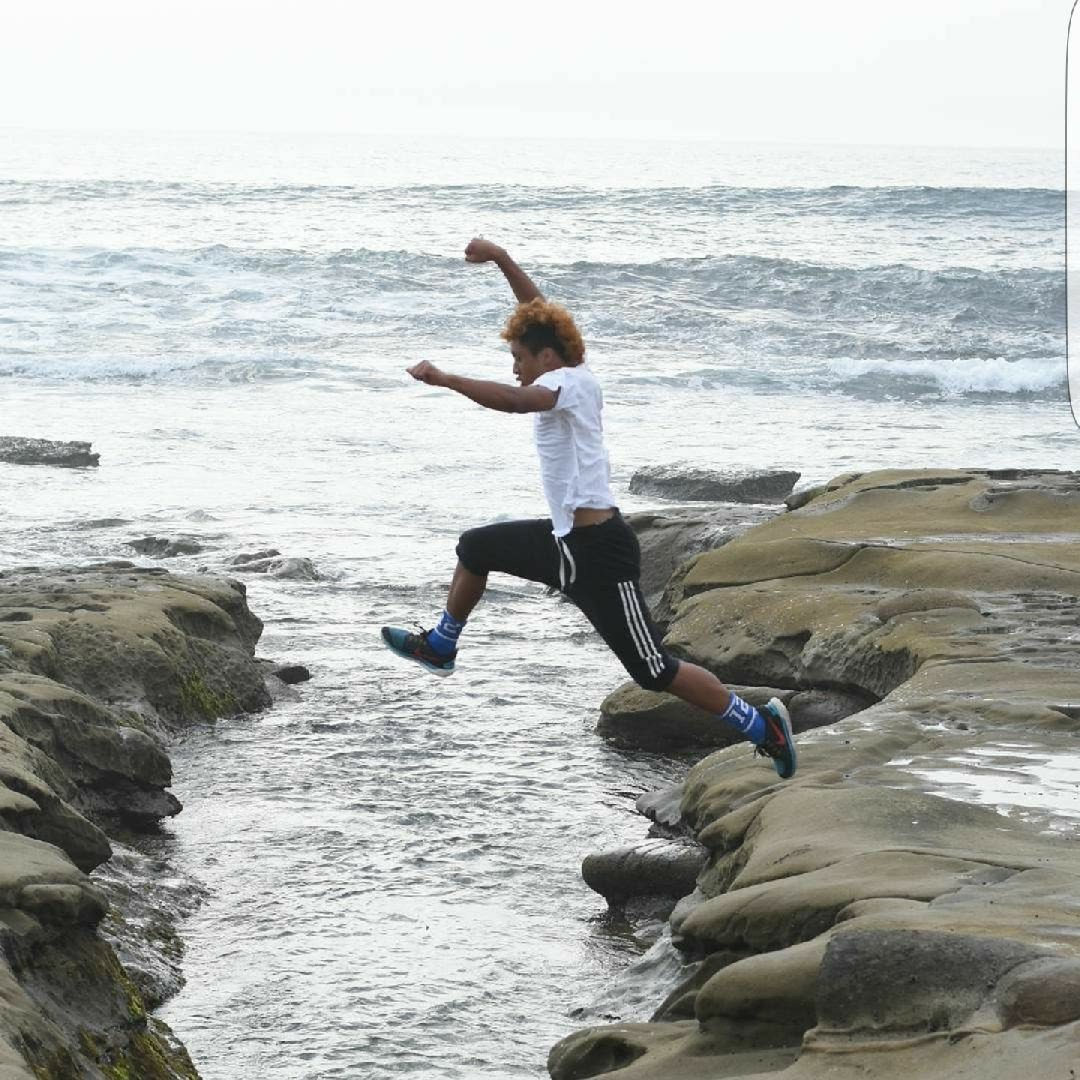 Ryan jumping over the water on the coast of Washington