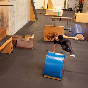 Belinda Garcia jumping over an obstacle in the gym