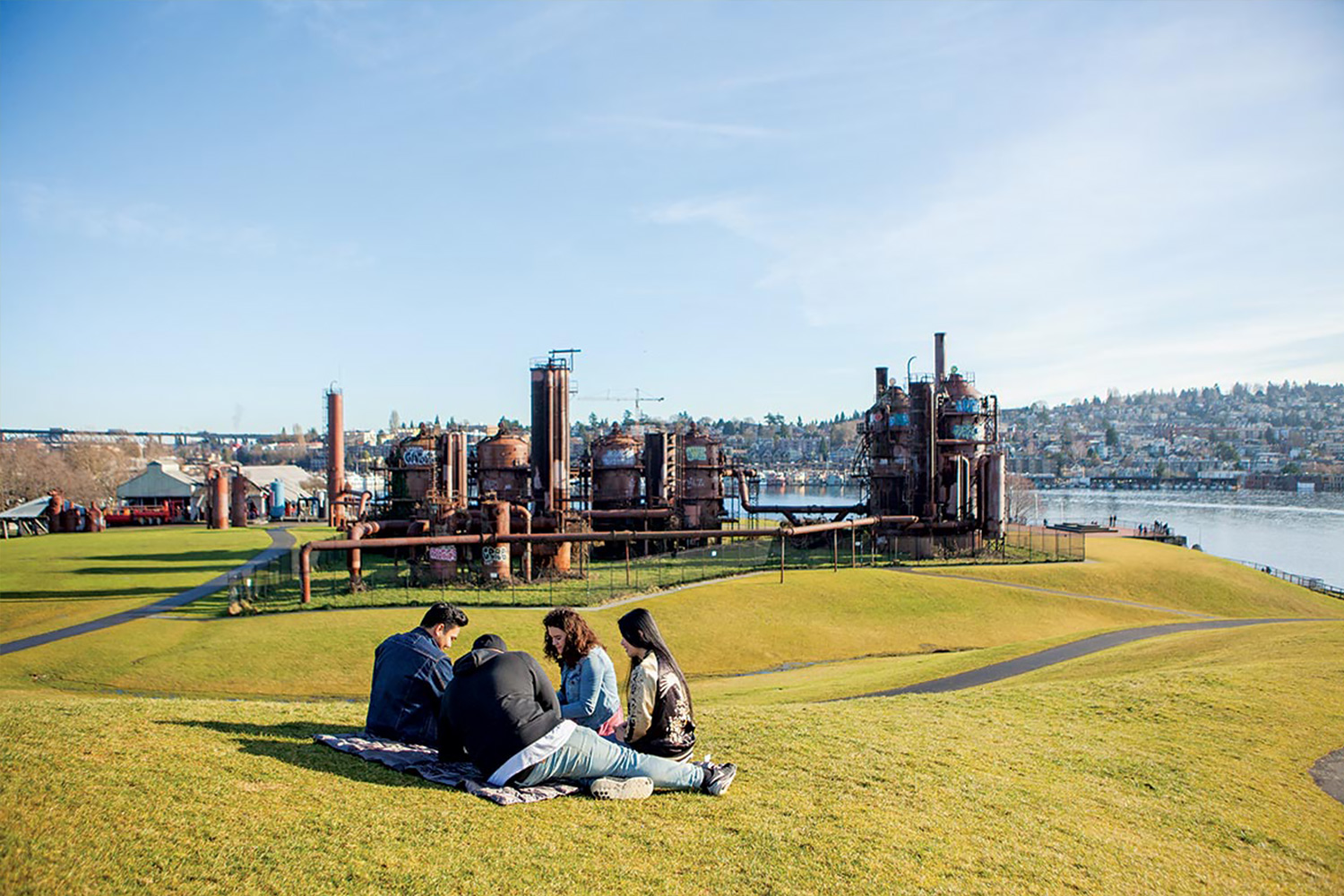 Students sitting on the grass in Gasworks Park, another fun thing to do in Seattle