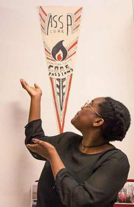 Lola Sosanya, SPU's 2016-17 student body president, points to a pennant describing the ASSP core.