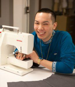 Nathan Samayo, apparel design and merchandising major sewing