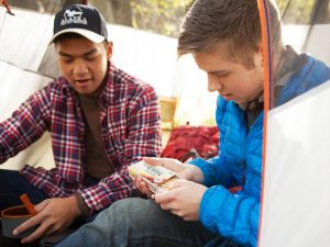 Brandon Pope and Andrew Baklund sitting, eating, and talking in a tent