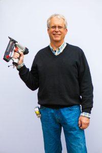 Roger Feldman, emeritus professor of art, holding a staple gun