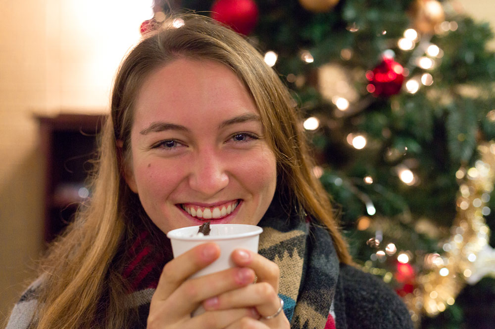 student smiles with hot chocolate