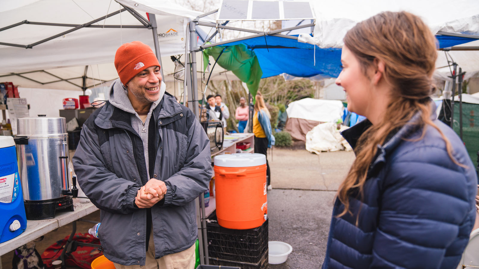 Micailah enjoys a conversation with a tent city 3 resident