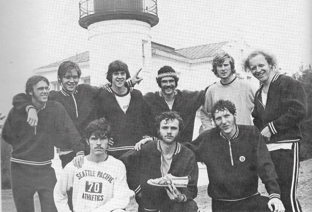 In this photo, a group of SPU students stand in front of the lighthouse near Camp Casey dressed in 1970s track clothing.