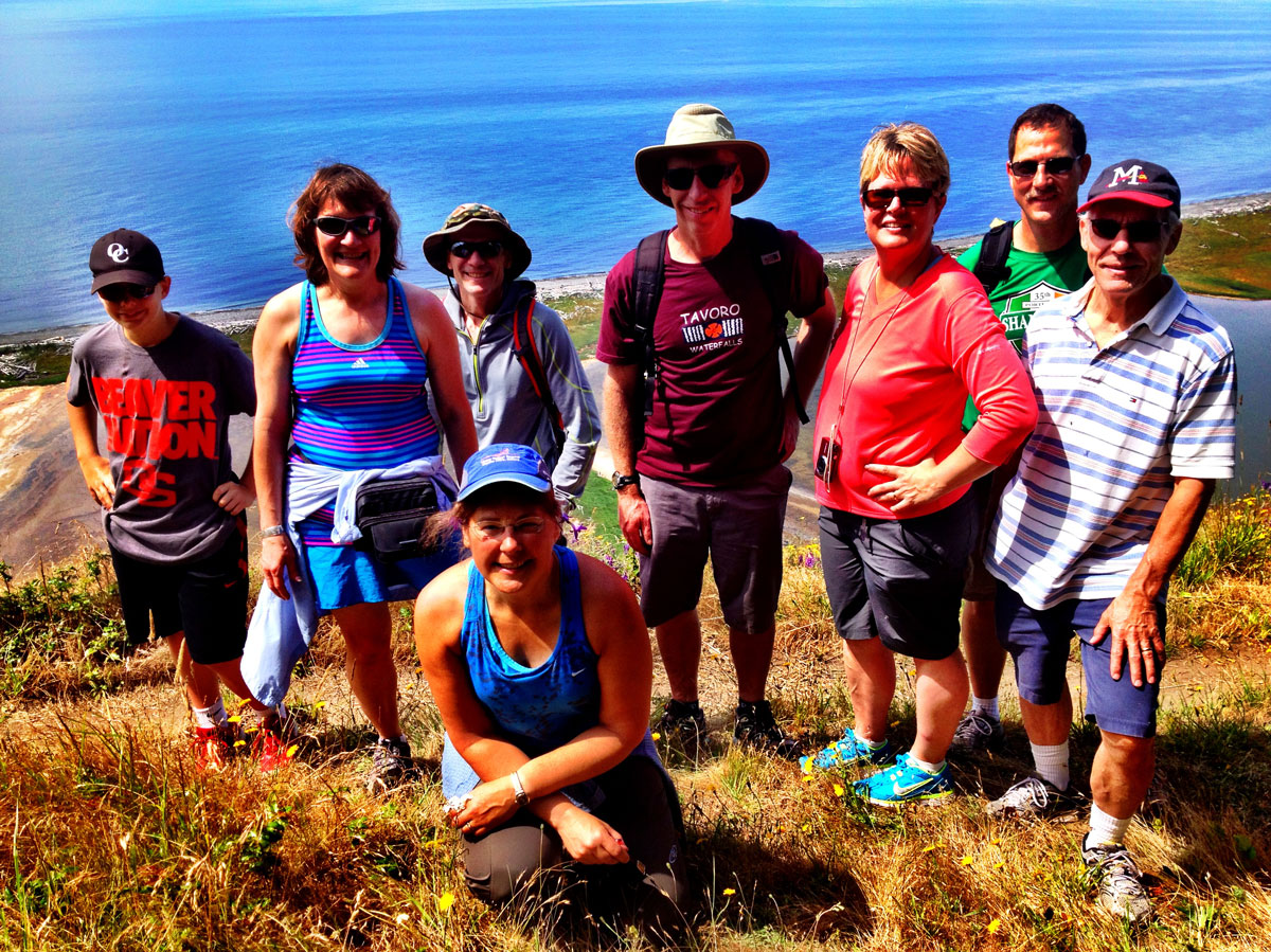 In this photo, a group of people stand on a grassy bluff overlooking water.