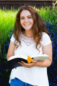 Kelsey Lucido poses for portrait holding a Bible