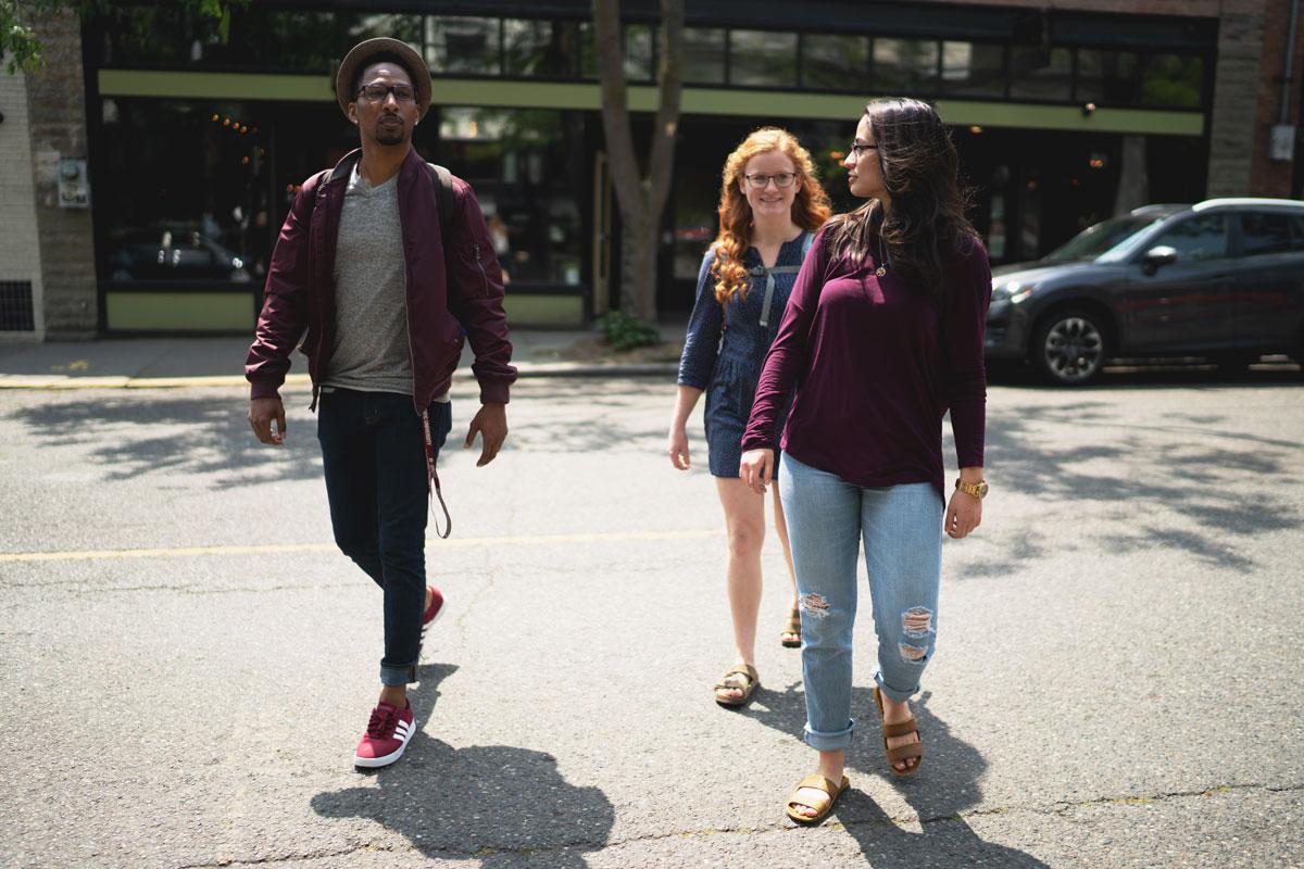 three students walk across a local neighborhood street