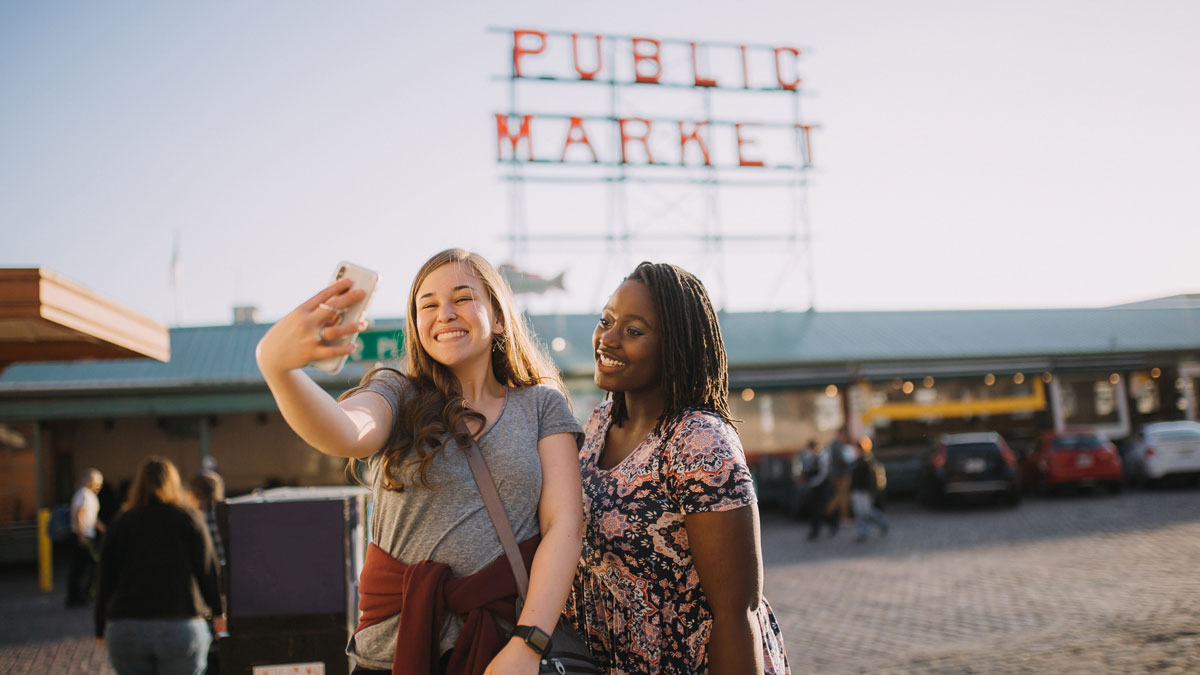 girl students pose for a selfie in front of public market sign