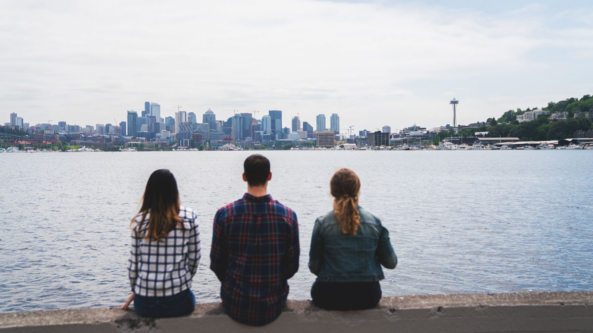 Three SPU students sitting at the edge south lake union looking at the Seattle skyline.