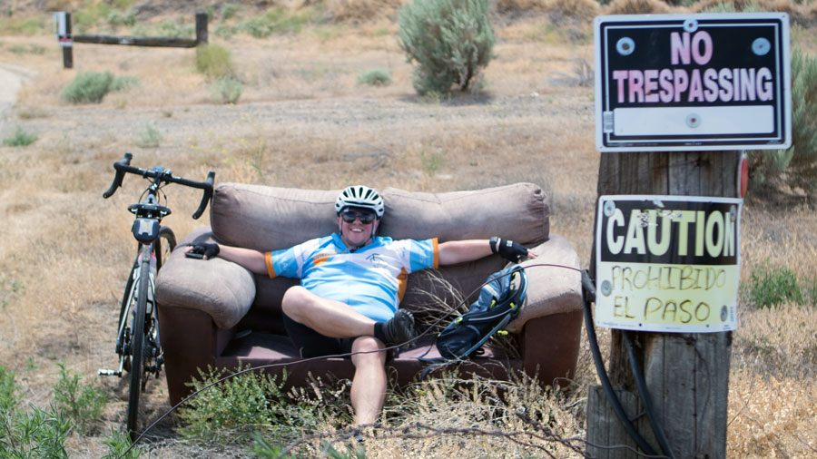 bicycler takes a break on an abandoned sofa outside