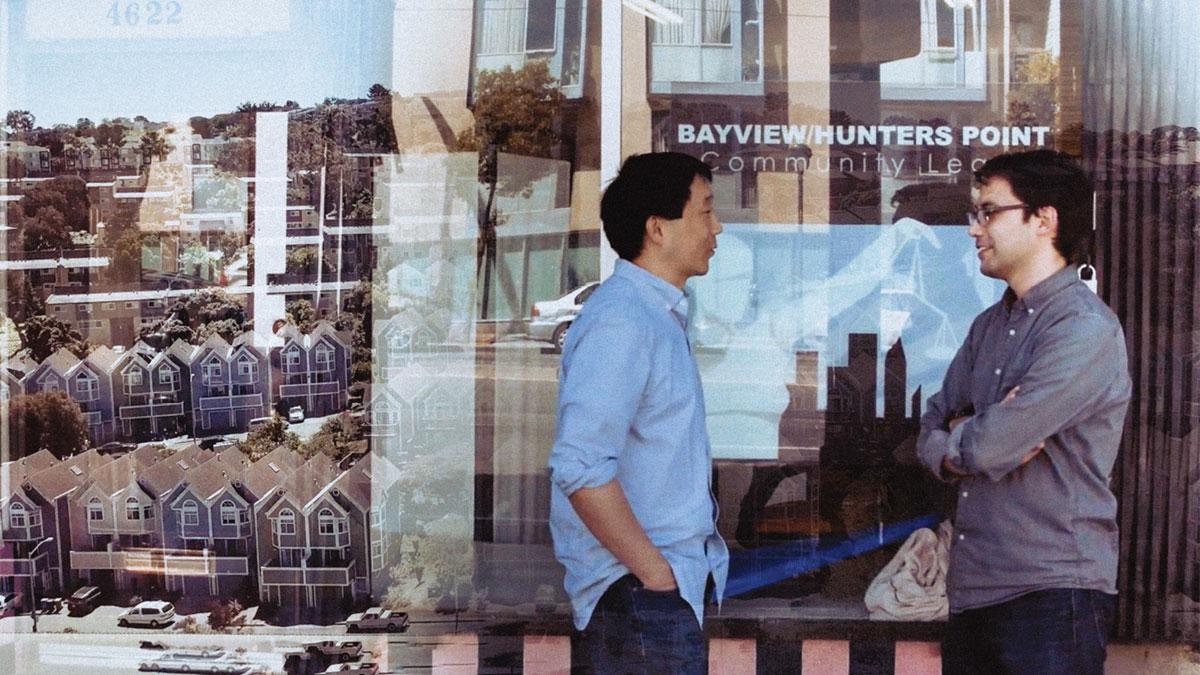 two men talking in front of window