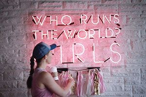 """A woman stands in front of a neon sign which reads """"Who runs the world? GIRLS"""""""