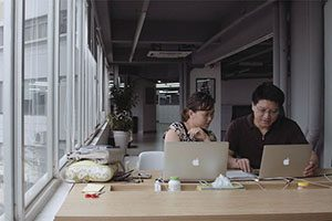A man and a woman work on a pair of laptops in a modern office space