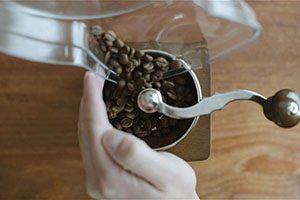 A hand guides coffee beans into a grinder