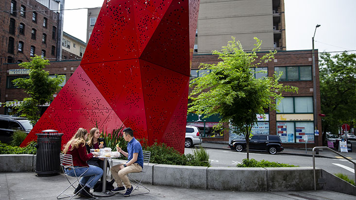 SPU students sit under a red sculpture in Seattle's International District - photo by Lindsey Wasson
