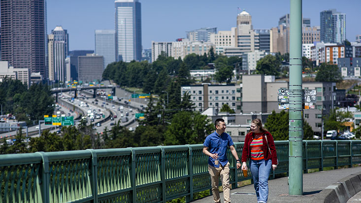 SPU students walk down the street with the Seattle skyline in the background - photo by Lindsey Wasson