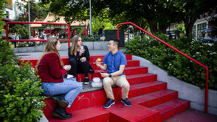 SPU students sit on red steps in the park - photo by Lindsey Wasson