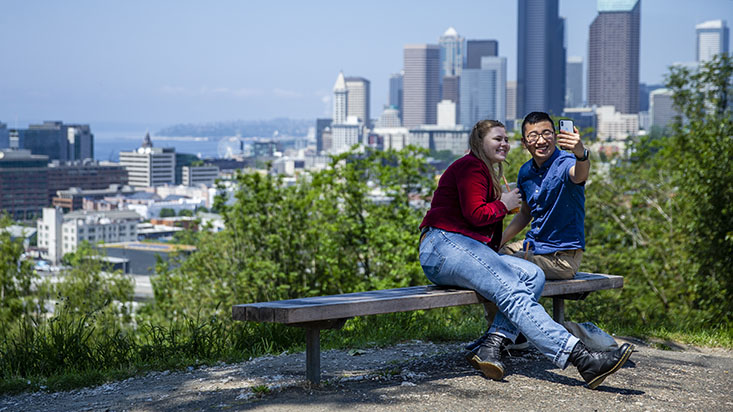 Two SPU students take a selfie with the Seattle skyline in the background - photo by Lindsey Wasson