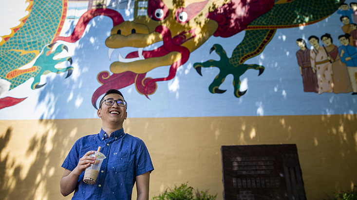 An SPU student stands by a wall with a dragon mural - photo by Lindsey Wasson
