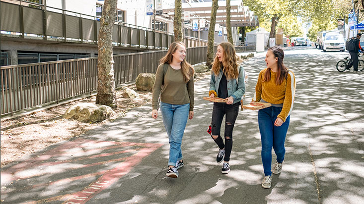 Three SPU students walk down the sidewalk in the Queen Anne neighborhood of Seattle