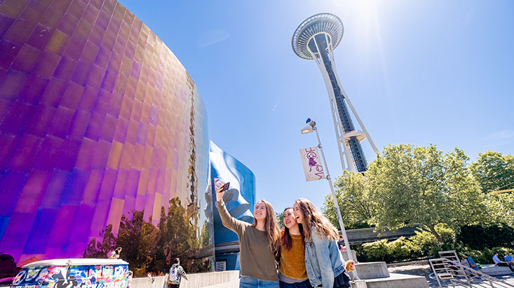 Three SPU students take a selfie by the Space Needle