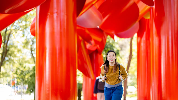 An SPU student walks under a large red sculpture by Seattle Center