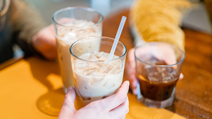 SPU students clink glasses of iced tea and coffee
