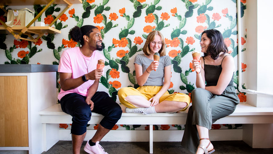friends eating ice cream in front of a colorful wallpaper