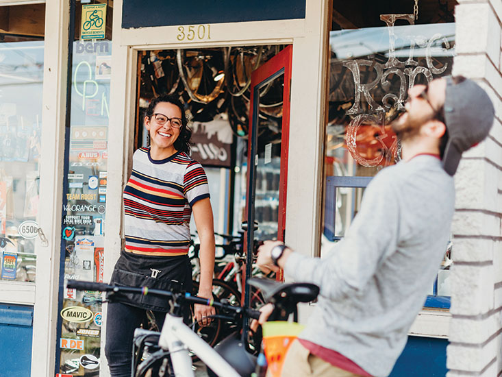 Shawna Williams laughs with a customer in front of Free Range Cycles | photo by Kendall Rock Photography