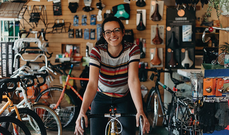 Shawna Williams sits on a bicyle in the middle of the sales floor of Free Range Cycles | photo by Kendall Rock Photography