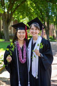 graduates pose with ivy vines