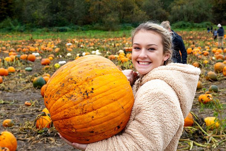An SPU student holds a pumpkin at Bob's Corn and Pumpkin Patch