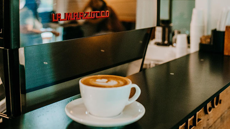 A freshly brewed latte sits on the counter at Aroma Coffee Co.