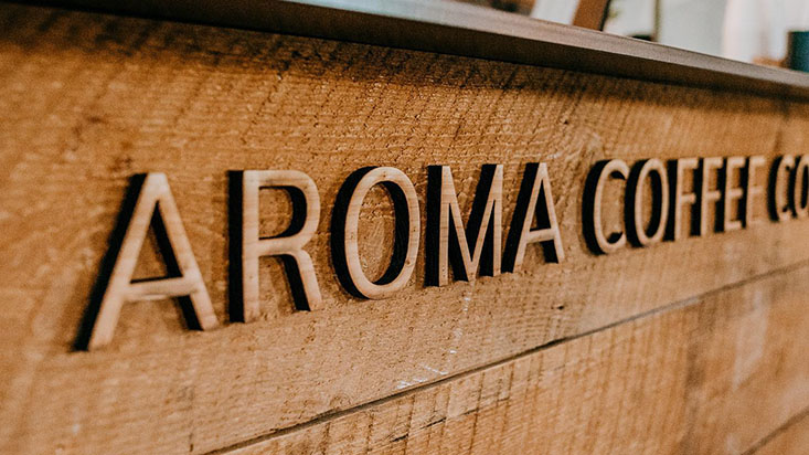 Aroma Coffee wooden sign at the front of the counter