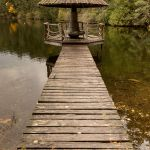 A wooden bridge leading to a wooden gazebo on a lake.