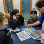 Associate Professor of Biology Rick Ridgway and his freshwater biology students examine maps of Blakely Island.