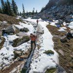 hikers cross melting snowfield